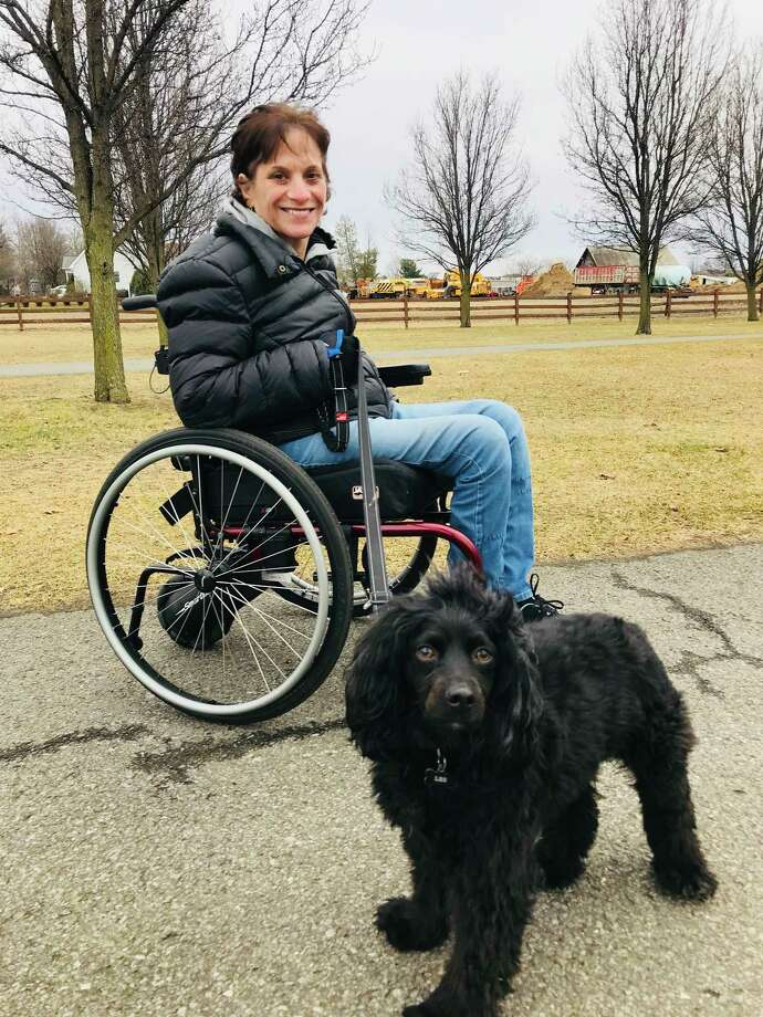 Nancy Ladd-Butz, who was severely injured and paralyzed by a falling boulder at Thacher Park last summer, is seen in her wheelchair at The Crossings in Colonie with her dog, Leo. (Paul Grondahl/Times Union)