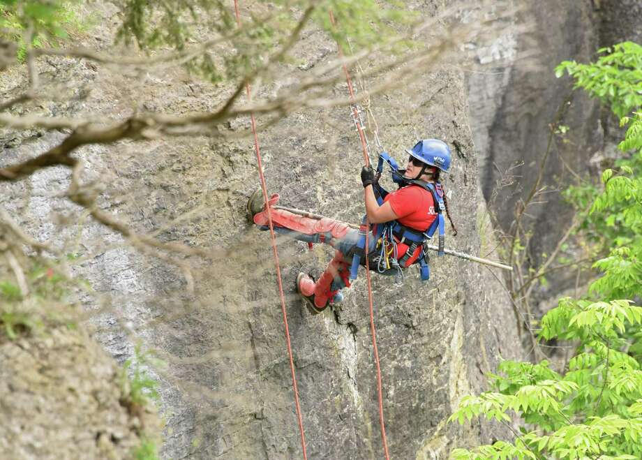 A female member of New York State Parks Recreation & Historic Preservation scaling team rappels down the rocky cliff above Indian Ladder Trail at John Boyd Thacher State Park on Thursday, May 31, 2018 in Voorheesville, N.Y. The scaling team, out of Ithaca, was poking loose rocks to make them fall to prevent future injuries to hikers. (Lori Van Buren/Times Union) Photo: Lori Van Buren