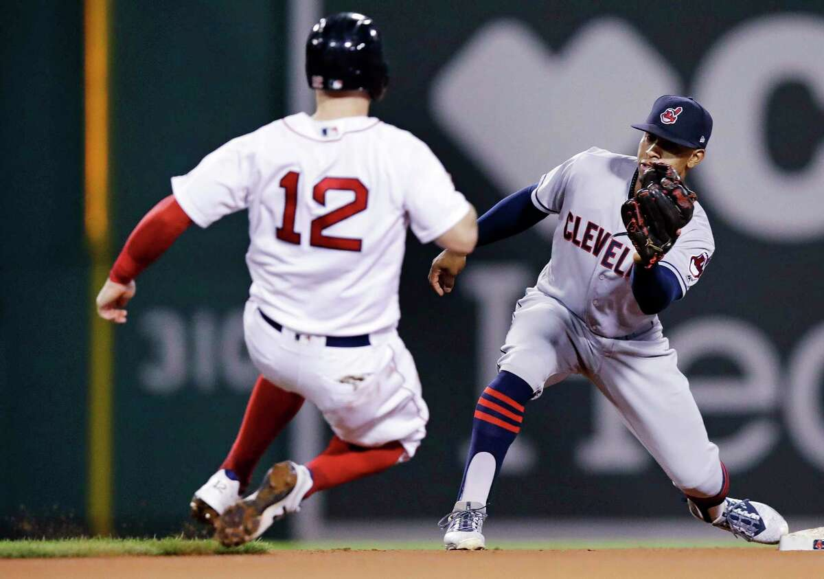 Cleveland Indians shortstop Francisco Lindor, right, fields the throw as he sets to tag out Boston Red Sox's Brock Holt (12) on a steal attempt during the fourth inning of a baseball game at Fenway Park in Boston, Monday, Aug. 20, 2018. (AP Photo/Charles Krupa)