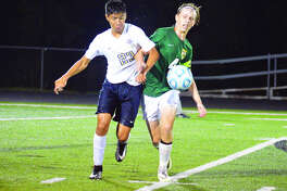 Father McGivney sophomore Diego Pacheco, left, battles for the ball with Metro-East Lutheran's Brent Woolsey on Monday night at Columbia High School in the Puma Bracket of the Metro Cup.