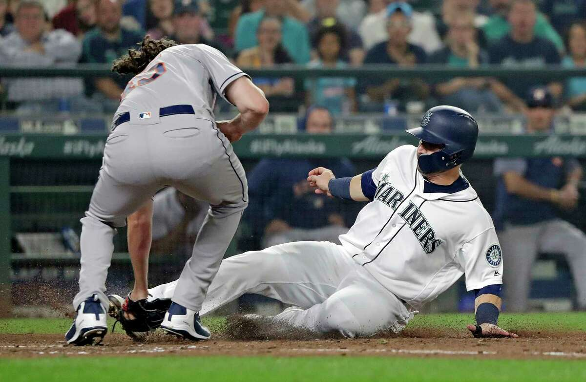 Seattle Mariners' Mike Zunino, right, slides into a tag at home by Houston Astros starting pitcher Gerrit Cole to end the fourth inning of a baseball game Monday, Aug. 20, 2018, in Seattle. (AP Photo/Elaine Thompson)