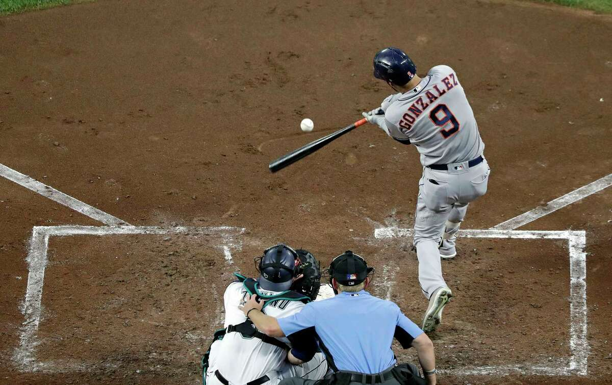 Houston Astros' Marwin Gonzalez hits a two-run double as Seattle Mariners catcher Mike Zunino and umpire Mike Muchlinski look on in the third inning of a baseball game, Monday, Aug. 20, 2018, in Seattle. (AP Photo/Elaine Thompson)