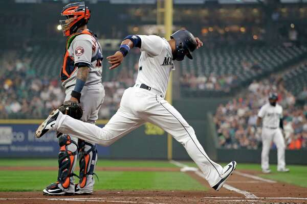 Seattle Mariners' Robinson Cano scores as Houston Astros catcher Martin Maldonado looks toward the field in the first inning of a baseball game Monday, Aug. 20, 2018, in Seattle. (AP Photo/Elaine Thompson)