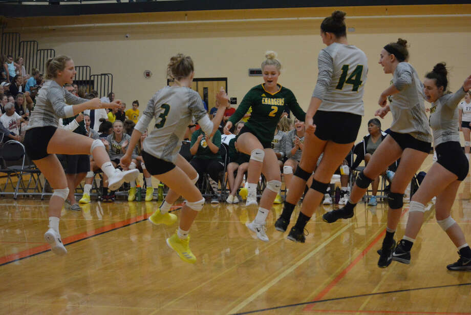 Dow High volleyball players celebrate a point during Saturday's tournament in Alma. (Photo provided)