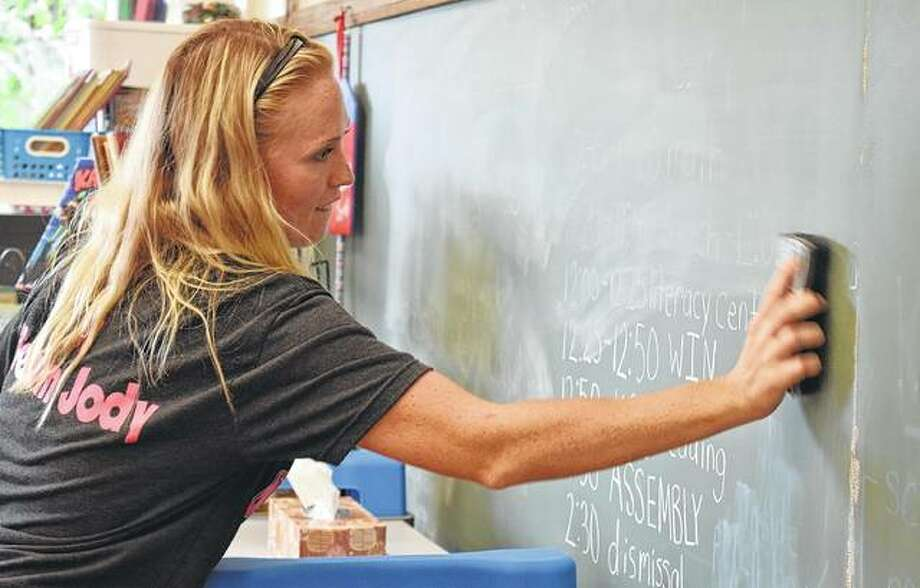 Morgan Zachary clears her chalk board Monday after the first day of school at Washington Elementary School. Photo:       Samantha McDaniel-Ogletree | Journal-Courier