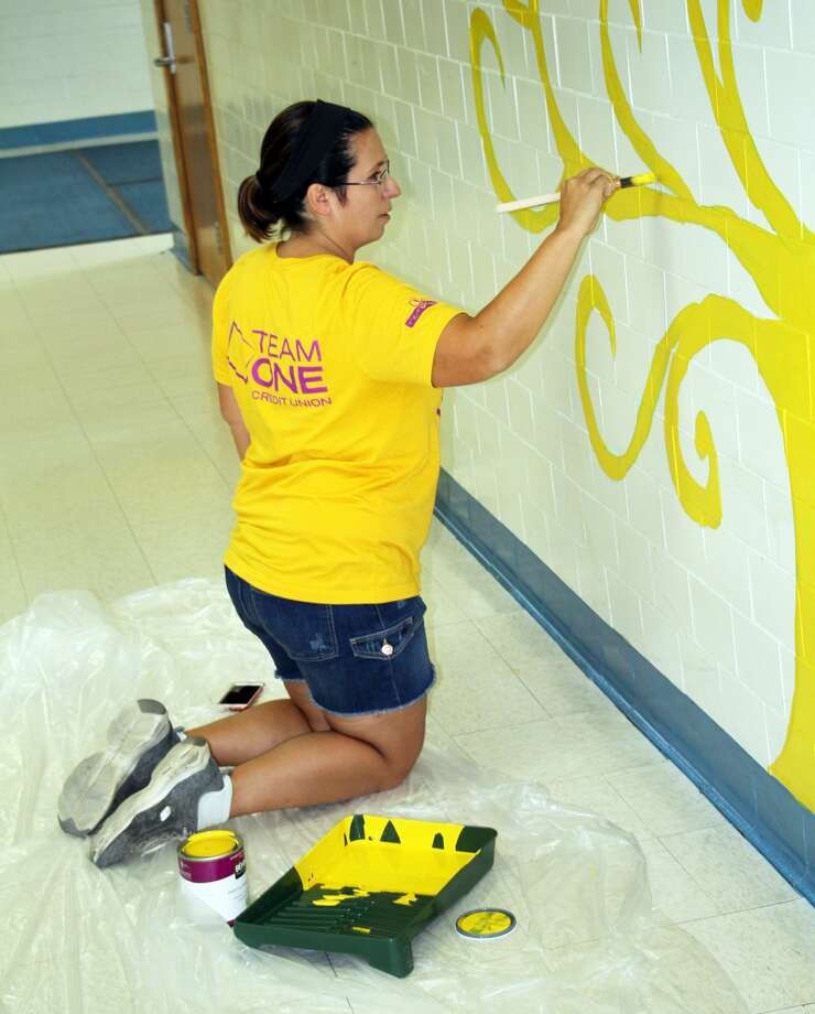 Local parent Melissa Checkley works on a tree mural at the Bad Axe Middle School, Monday morning. Volunteers showed up to help paint several walls at the school, which will be used by students to show off various projects throughout the year. Photo: Seth Stapleton/Huron Daily Tribune