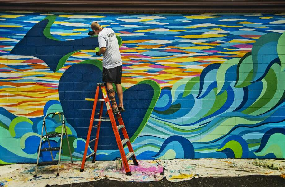 Mark Piotrowski of Bay City, owner of MARKed Arts, puts the finishing touches on a mural at Great Lakes Pharmacy of Midland at the corner of Eastman and Bookness on Monday, Aug. 20, 2018. (Katy Kildee/kkildee@mdn.net) Photo: (Katy Kildee/kkildee@mdn.net)