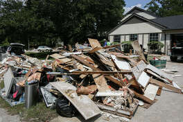 Piles of debris line the streets of the River Plantation community as homeowners and volunteers strip out unsalvageable furniture, drywall, carpet and more from homes flooded during Tropical Storm Harvey on Saturday, Sept. 2, 2017, in Conroe.
