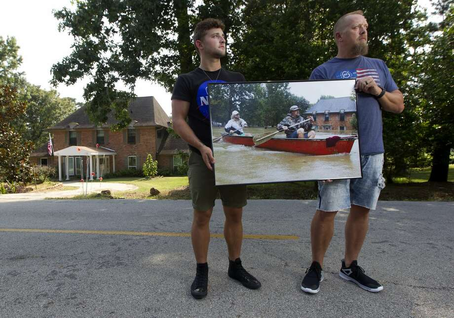 Josh and Levi Curnel pose for a portrait holding an image of them paddling down Stonewall Jackson Drive during Hurricane Harvey on Thursday, July 26, 2018, in Conroe. The Curnel's returned to the site where the image was taken nearly a year after Harvey flooded their home and much of the River Plantation community. Photo: Jason Fochtman/Staff Photographer