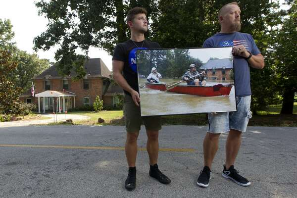 Josh and Levi Curnel pose for a portrait holding an image of them paddling down Stonewall Jackson Drive during Hurricane Harvey on Thursday, July 26, 2018, in Conroe. The Curnel's returned to the site where the image was taken nearly a year after Harvey flooded their home and much of the River Plantation community.