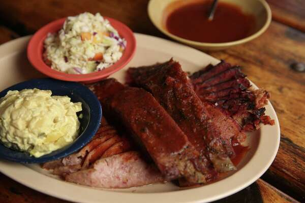 The Sampler plate from Hickory Hollow's original Fallbrook location has beef brisket, sausage and ribs with side dishes of potato salad and coleslaw on Friday, Dec. 1, 2017, in Houston. ( Yi-Chin Lee / Houston Chronicle )