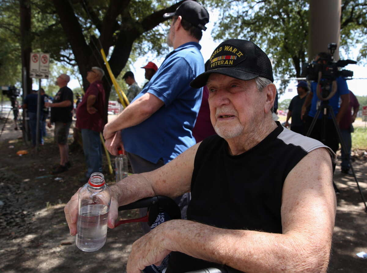 World War II veteran Hawk McGinnis, 90, takes a sip of water after being evacuated from his veteran housing apartment due to a fire on the roof of the building at 4000 block of Travis Street , Aug. 21, 2018, in Houston. McGinnis said HFD firefighters carried him down from his third floor apartment. No one was injured.