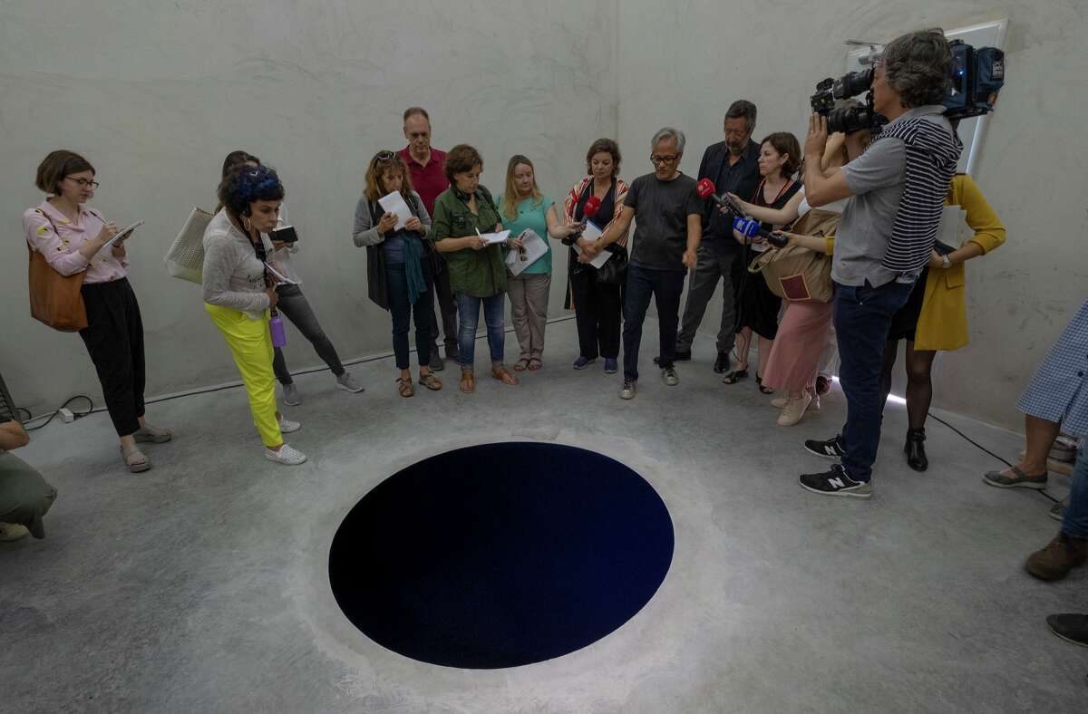 Artist Anish Kapoor talks to journalists inside the cube structure of