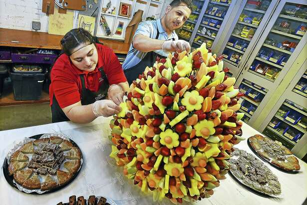Fouad Elgoute, owner of Hamden Edible Arrangements, at right, and his store manager, Saba Shanawar, put the finishing touches on a three-foot tall, 65 pound edible arrangement at the Eli WhitneyMuseum's 23rd annual Leonardo in Bloom Challenge fundraiser in 2017.