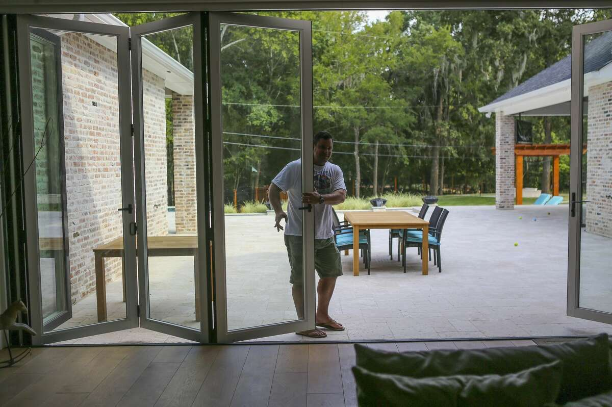 Todd Jones opens sliding doors onto the patio of his family's new home along a short tributary of the Buffalo Bayou, Thursday, July 26, 2018 in Houston. The Jones family was about to move into their newly built home in Nottingham Forest when floodwaters filled the almost-completed home with three feet of water. A year later, they've just moved in becoming one of the few families to re-occupy this badly flooded neighborhood.