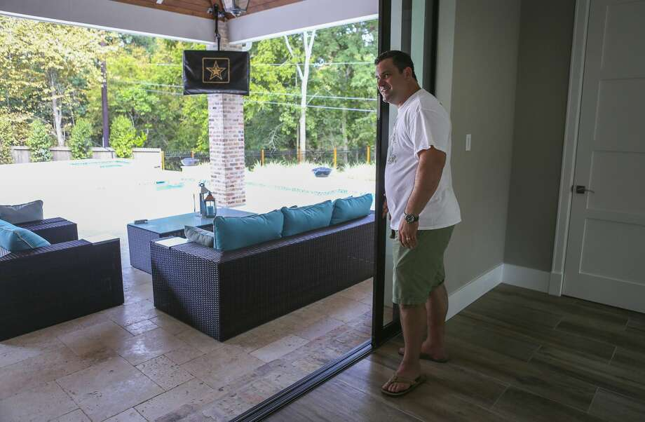 Todd Jones opens sliding doors from his game room to the patio of his family's new home along a short tributary of the Buffalo Bayou, Thursday, July 26, 2018 in Houston. The Jones family was about to move into their newly built home in Nottingham Forest when floodwaters filled the almost-completed home with three feet of water. A year later, they've just moved in becoming one of the few families to re-occupy this badly flooded neighborhood. Photo: Mark Mulligan