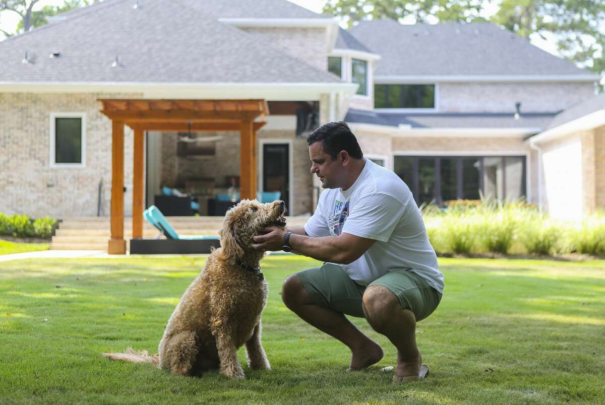Todd Jones plays with the family dog, Hudson, in the backyard of their new home along a short tributary of the Buffalo Bayou, Thursday, July 26, 2018 in Houston. The Jones family was about to move into their newly built home in Nottingham Forest when floodwaters filled the almost-completed home with three feet of water. A year later, they've just moved in becoming one of the few families to re-occupy this badly flooded neighborhood.
