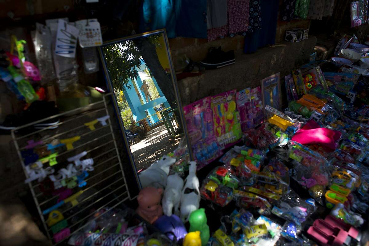In this Aug. 18, 2018 photo, a statue of a young migrant traveling to the U.S. is reflected in a shop mirror, on the central square in Intipuca, El Salvador. The hero statue is in the town's main plaza, Parque Los Emigrantes, or Immigrants Park, and carries a backpack. (AP Photo/Rebecca Blackwell)
