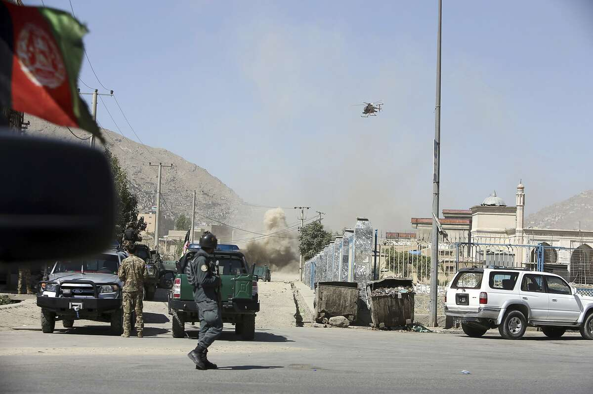 A military helicopter targets a house where attackers fired rockets toward the presidential palace in the capital, Kabul.