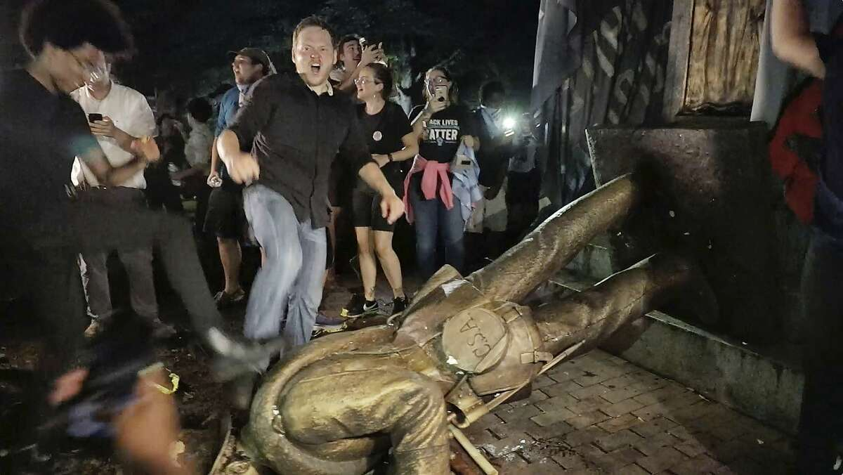 """Protesters celebrate after the Confederate statue known as """"Silent Sam"""" was toppled on the campus of the University of North Carolina in Chapel Hill, N.C., Monday, Aug. 20, 2018. (Julia Wall/The News & Observer via AP)"""