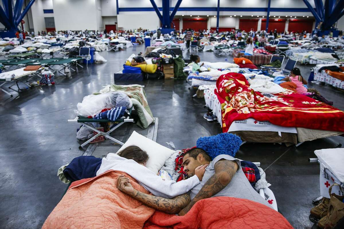 Tammy Dominguez, left, and her husband, Christopher Dominguez, sleep on cots at the George R. Brown Convention Center where nearly 10,000 people are taking shelter after Hurricane Harvey Wednesday, Aug. 30, 2017 in Houston. They have been at the shelter since evacuating Houston's Northside on Sunday.