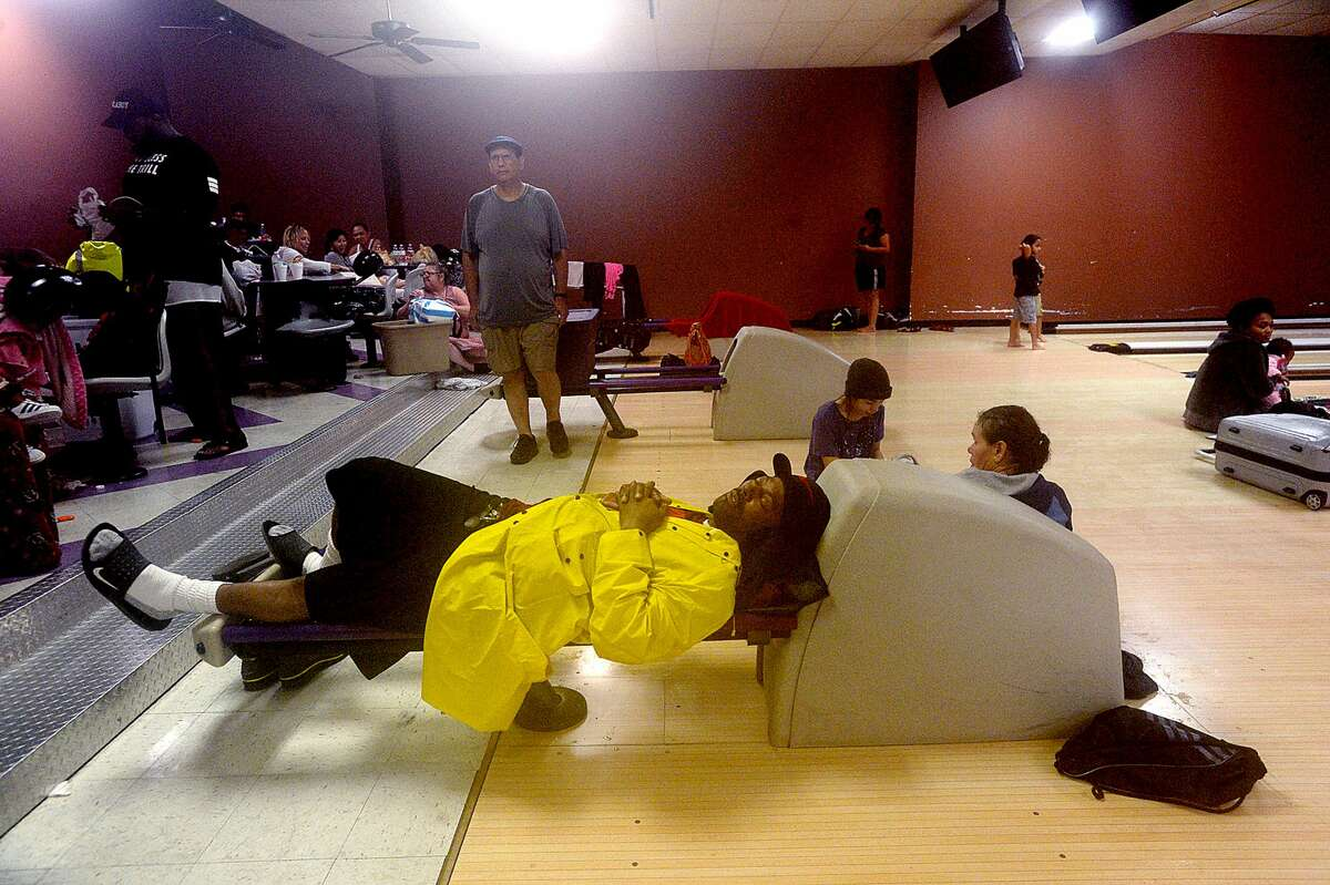 A man sleeps on one of the bowling ball returns as evacuees continue to pour into the Max Bowl, which was converted to a shelter for those displaced by flooding in Port Arthur Wednesday, August 30, 2017.