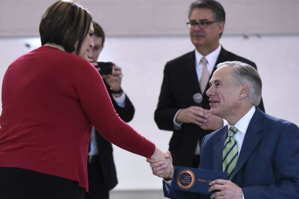 Amber Simpson, master teacher at Barrera Veterans Elementary School in the Somerset Independent School District, is greeted by Texas Gov. Greg Abbott, after she was named the recipient of the $25,000 Milken Educator Award on Tuesday, Feb. 7, 2017.