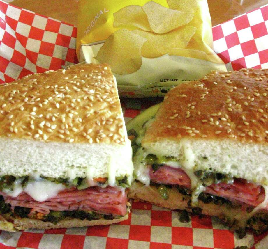 The Hearthstone Lotta Muffaletta from Hearthstone Bakery Cafe is stacked with your choice of ham and salami or turkey, layered with diced olives and veggies, provolone cheese and toasted. Photo: Staff File Photo / JMCINNIS@EXPRESS-NEWS.NET