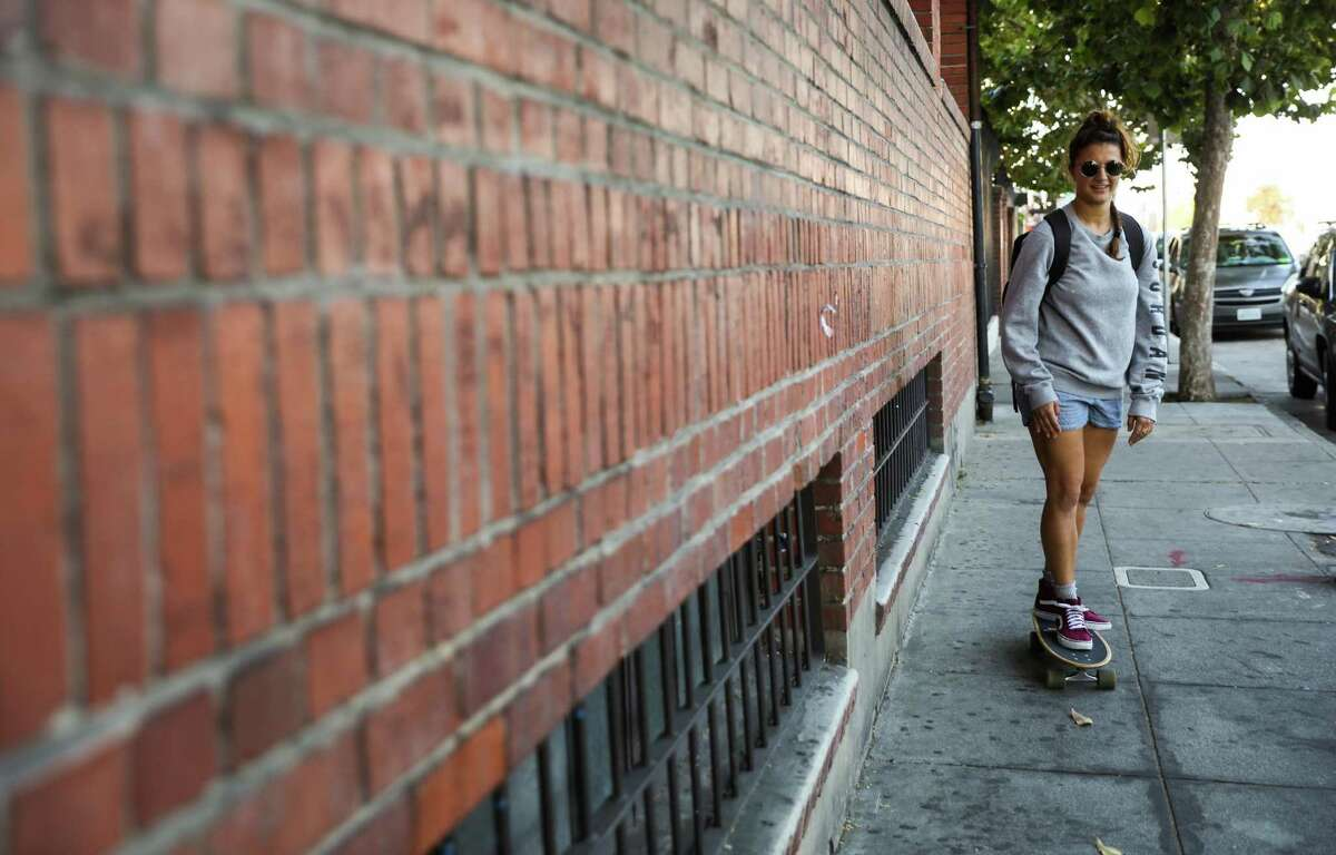 Courtney Hope, 27 rides her skateboard to the BART train as she makes her way home after taking a dance class at the City Dance Annex in San Francisco, California, on Thursday, Aug. 2, 2018.
