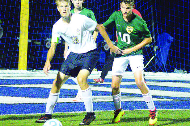 Father McGivney senior Nate Dammerich, left, eyes the ball during his team's season opener against Metro-East Lutheran on Tuesday in Columbia.