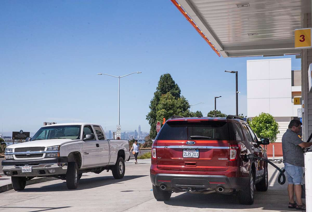 A man pumps gas into his SUV while a large truck waits its turn at the Shell station near Powell Street and West Frontage Road in Emeryville, Calif. Saturday, Aug. 4, 2018.