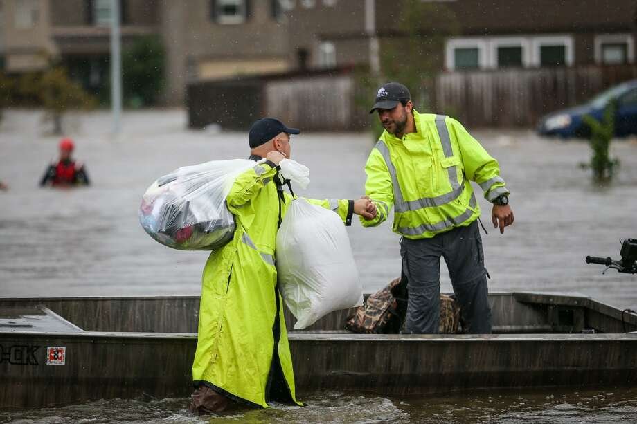 Montgomery County Precinct 1 Constable's deputy Paul Bostick, left, thanks Tyler resident Casey Korkmas and the other volunteer boaters from Tyler for their help in water rescues during Tropical Storm Harvey on Tuesday, Aug. 29, 2017, in the Montgomery Creek Ranch subdivision of Conroe. Photo: Michael Minasi, Staff Photographer / Houston Chronicle / © 2017 Houston Chronicle