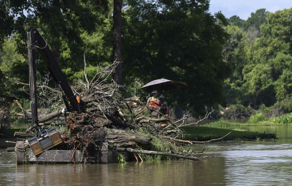 A Lake Houston debris removal barge heading back to the landing after collecting debris for about an hour on July 6, 2018, in Huffman. Mitigation projects like these would be funded by a $2.5 billion bond proposal on the ballot Saturday. ( Yi-Chin Lee / Houston Chronicle )