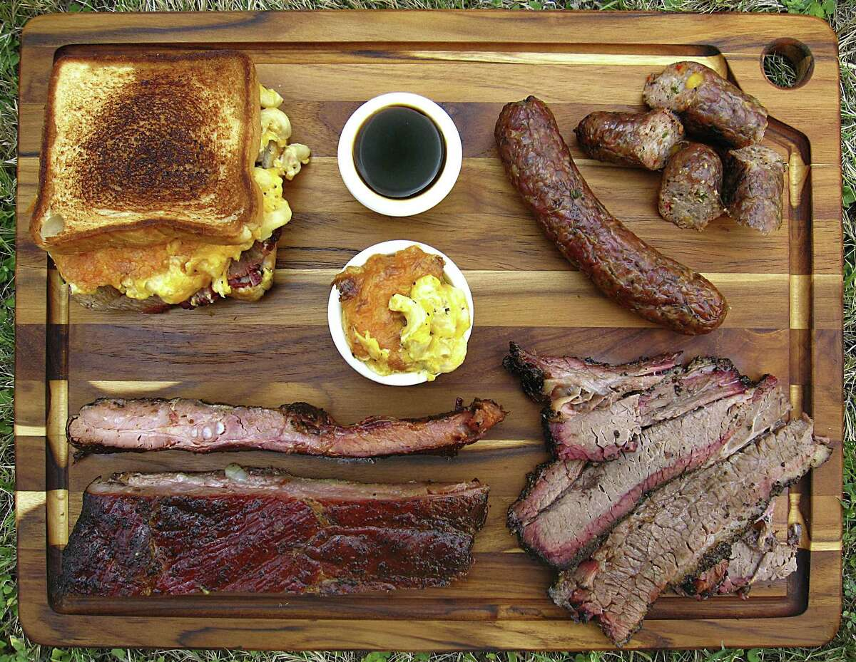 Barbecue and sides from Nelson's BBQ. Clockwise from top left: Nasty Nate sandwich with brisket and mac and cheese, barbecue sauce, handmade spicy sausage, fatty and lean brisket, pork spare ribs and macaroni and cheese.
