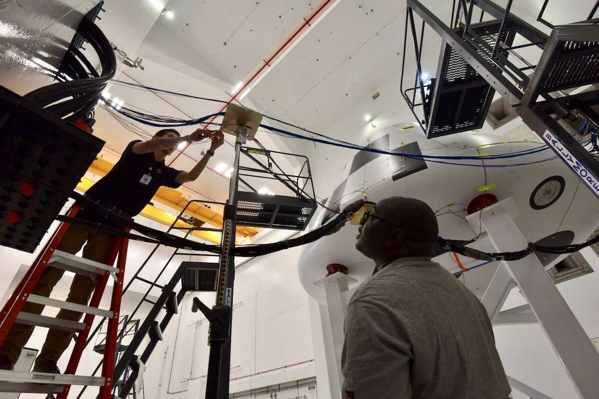 NASA personnel connect power and sensor cables used to track data during acoustic testing at NASA Glenn Research Center's Plum Brook Station in Sandusky, Ohio, on Aug. 21, in preparation for Orion's Ascent Abort-2 test.