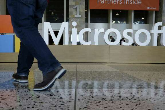In this April 28, 2015, file photo, a man walks past a Microsoft sign set up for the Microsoft BUILD conference at Moscone Center in San Francisco. Microsoft has uncovered new hacking attempts by Russia targeting U.S. political groups ahead of the midterm elections. The company said Tuesday, Aug. 21, 2018, that a group tied to the Russian government created fake websites that appeared to spoof two American conservative organizations: the Hudson Institute and the International Republican Institute. Three other fake sites were designed to look as if they belonged to the U.S. Senate.