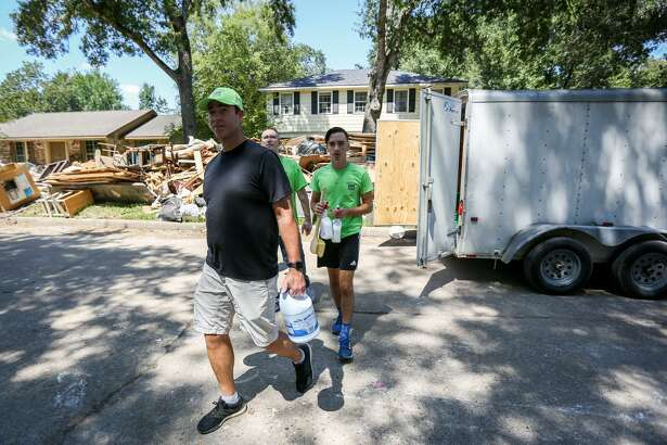 David Knox, left, and his son Carson, right, both volunteers from North Woodlands Area Church of Christ, carry cleaning supplies to a Woodloch resident's home on Sunday, September 10, 2017.