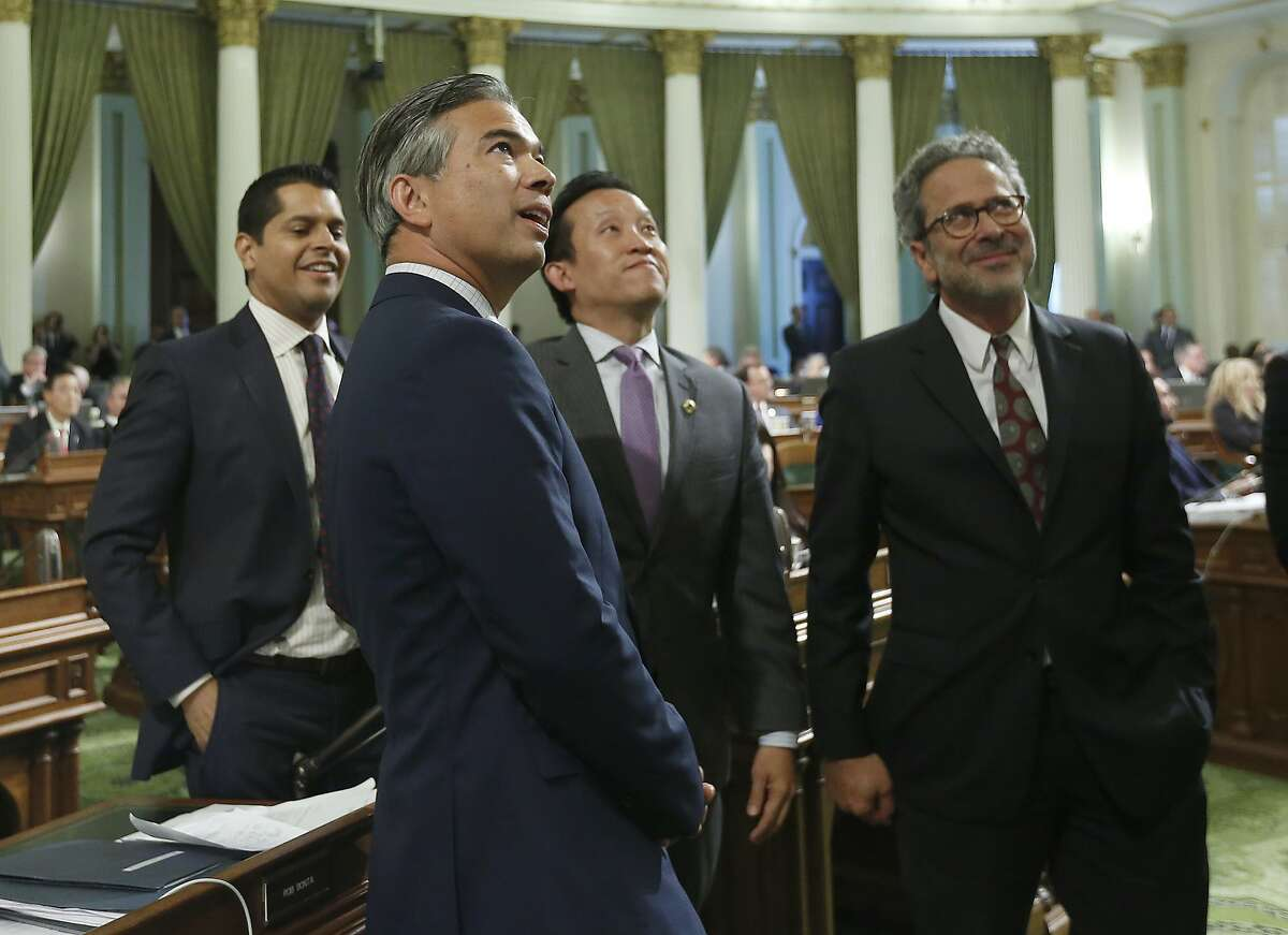 Assemblyman Rob Bonta, D-Alameda (second from left), watches the posting of votes as the bill passes the Assembly.