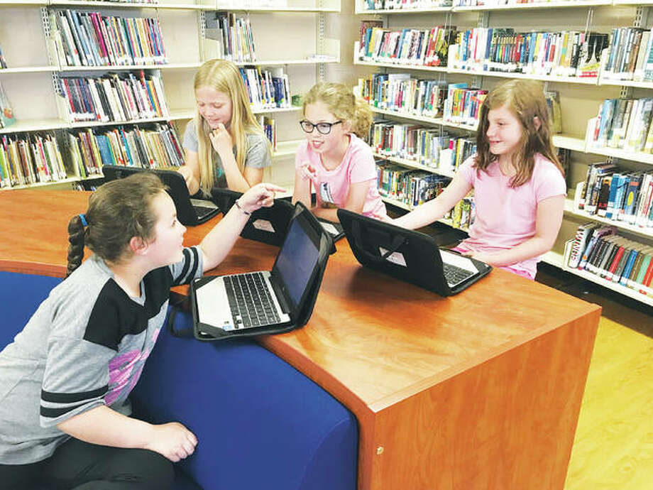 Mount Olive third-grade students, left to right, Alexis Mielke; Jennifer Kofowski; Ava Baumberger; and, Jada Foster work together as a cooperative group on their Chromebooks, while seated comfortable among the Mount Olive public school library, recently transformed to a modern media center. Approximately 50 volunteers did the work to revitalize the school library. Photo:       For The Telegraph