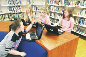 Mount Olive third-grade students, left to right, Alexis Mielke; Jennifer Kofowski; Ava Baumberger; and, Jada Foster work together as a cooperative group on their Chromebooks, while seated comfortable among the Mount Olive public school library, recently transformed to a modern media center. Approximately 50 volunteers did the work to revitalize the school library.