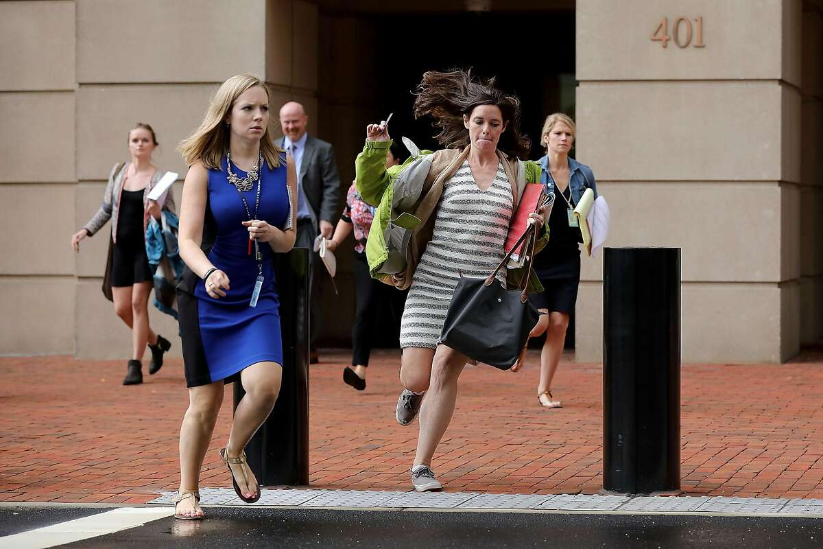 ALEXANDRIA, VA - AUGUST 21: Journalists run out of the Albert V. Bryan U.S. Courthouse during the trial of former Trump campaign chairman Paul Manafort during the fourth day of jury deliberation August 21, 2018 in Alexandria, Virginia. Manafort has been charged with bank and tax fraud as part of special counsel Robert Mueller's investigation into Russian interference in the 2016 presidential election. (Photo by Chip Somodevilla/Getty Images)