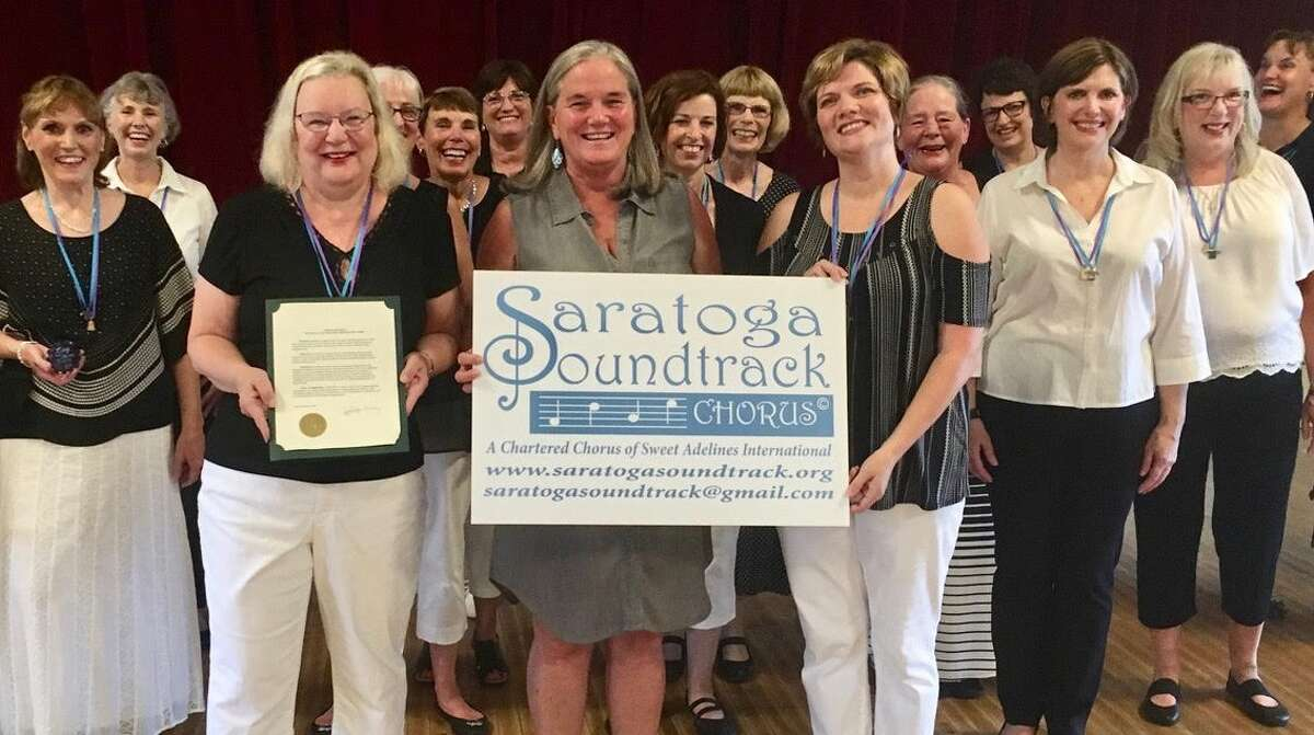 Saratoga Springs Mayor Meg Kelly reads a proclamation honoring Saratoga Soundtrack Chorus? accomplishments to celebrate their 10th year anniversary, as a contributing organization to the city. (Margaret McIntyre)