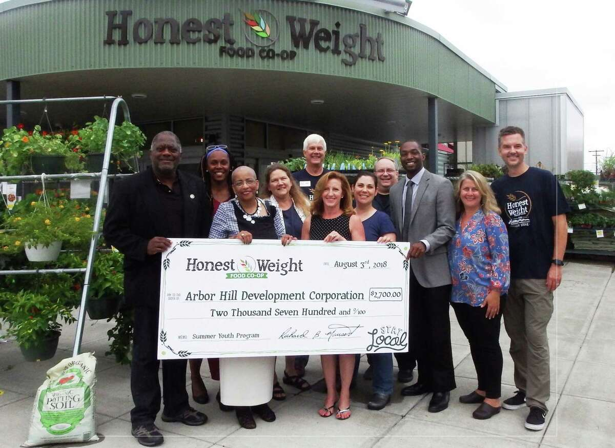 Honest Weight Food Co-op presented a check this month totalling $2,700 to the Arbor Hill Development Corporation in Albany in support of their efforts to launch a baseball and softball league for youth Arbor Hill and the surrounding neighborhoods. (Submitted photo)