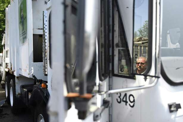 """Fleet Manager Michael Scacco is reflected in the side mirror as he shows one of the garbage trucks that will be used for leaf collection at the Stamford Fleet Maintenance center in Stamford, Conn. Tuesday, Aug. 21, 2018. As a cost-saving measure, Stamford will deploy three garbage trucks to collect bagged leaves instead of the using the large leaf """"vacuums"""" as in the past. The trucks were used as backups before and are getting standard maintenance done to get their capacities on par with the rest of the fleet."""