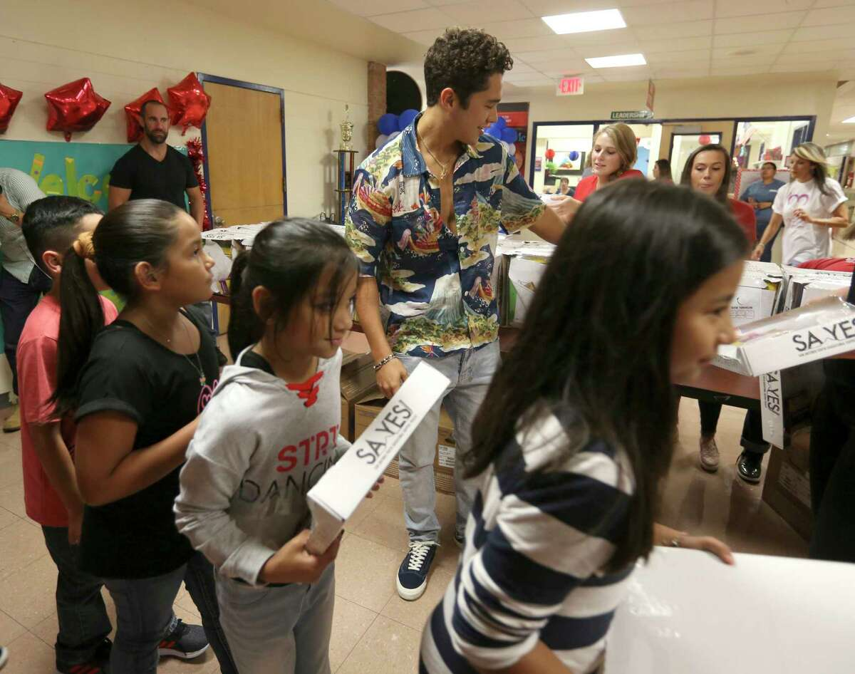 San Antonio native Austin Mahone, center, distributes school supplies Tuesday, Aug. 21, 2018 at Palo Alto Elementary on the city's south side. The supplies were given to the school from the San Antonio Youth Educational Support Project through private and corporate donors, according to the organization's press release.