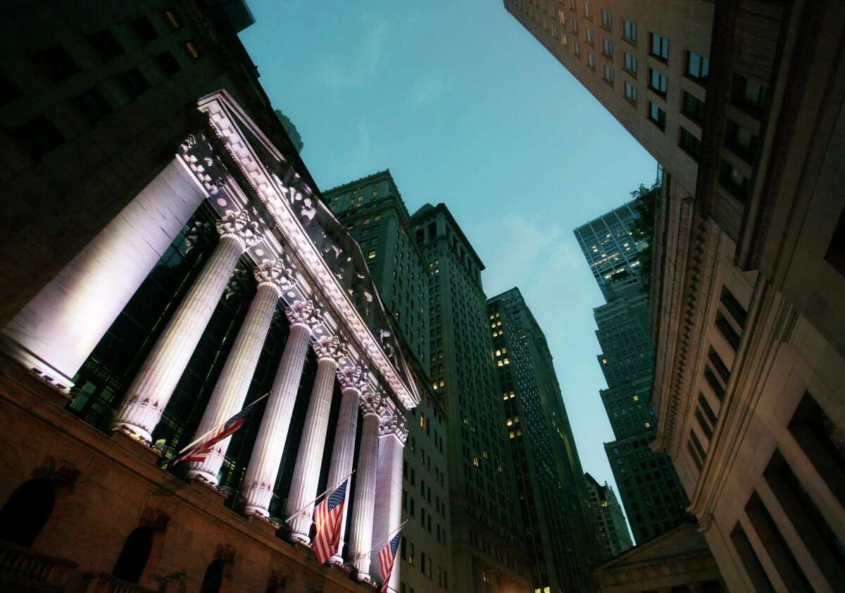 FILE - In this Oct. 8, 2014, file photo, American flags fly in front of the New York Stock Exchange. The U.S. stock market opens at 9:30 a.m. EST on Tuesday, Aug. 21, 2018. (AP Photo/Mark Lennihan, File)