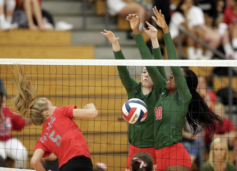 Oak Ridge's Brianna Rhodes (5) has her spike blocked by The Woodlands' Amelia Opeenheimer and Amanda Ifeanyi (10) during their varsity volleyball game at The Woodlands High School Tuesday. Photo: Michael Wyke / Contributor / © 2018 Houston Chronicle