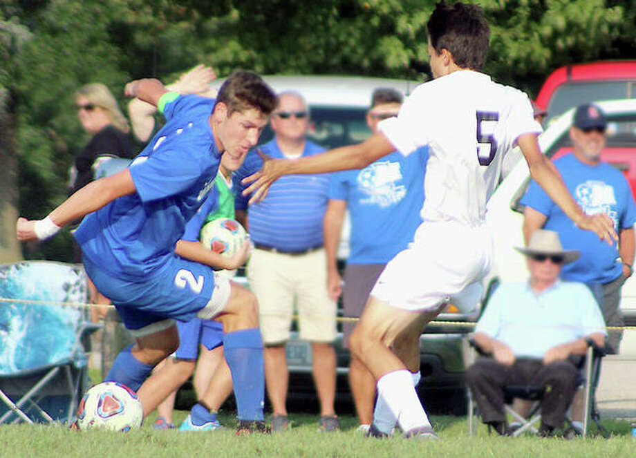 Marquette's Chris Hartrich, left, battles for the ball with Triad's Austin Borri Tuesday at Gordon Moore Park. Hartrich scored for the Explorers in the 1-1 non-conference draw. Photo:     Pete Hayes | The Telegraph
