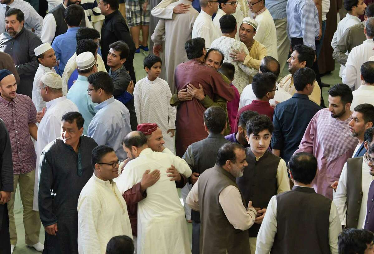 Muslims embrace each other following prayers to celebrate Eid ul Adha at the Islamic Center of the Capital District on Tuesday, Aug. 21, 2018, in Colonie, N.Y. (Paul Buckowski/Times Union)