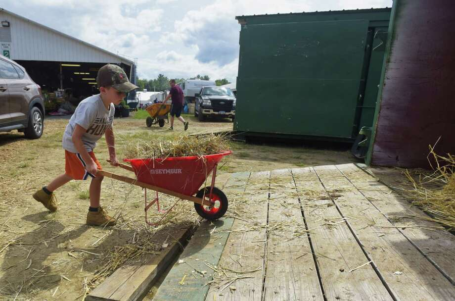 Charlie Gilchrist, 6, from Shushan dumps used bedding from the stalls at the Washington County Fair on Monday, Aug. 20, 2018, in Greenwich, N.Y. Charlie will show his heifer calf on Thursday and Friday. The fair runs through Sunday, Aug. 26th.   (Paul Buckowski/Times Union) Photo: Paul Buckowski / (Paul Buckowski/Times Union)